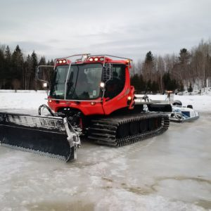 Machine grooming snowmobile trail